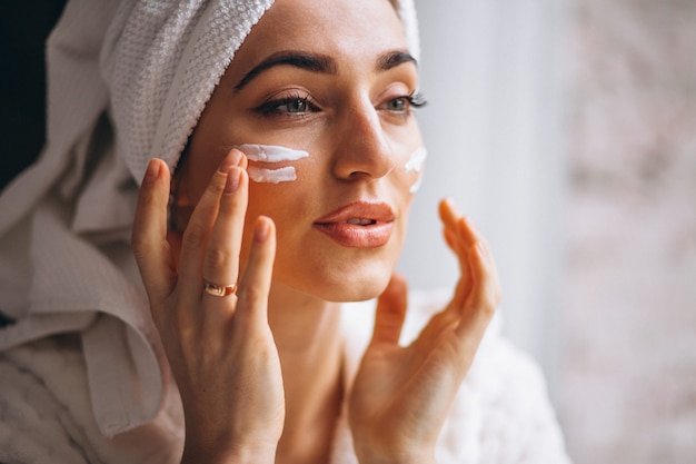 Mujer aplicar crema facial