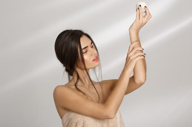 Mujer aplicar crema hidratante en la mano izquierda después del baño. cuidado de la belleza.