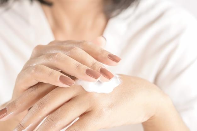 Mujer aplicar crema en mano