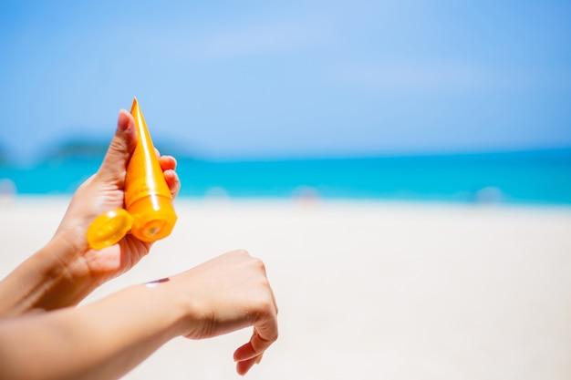 Mujer aplicar crema de protección solar contra el mar caribe turquesa