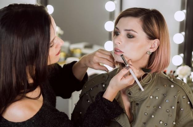 Mujer aplicar lápiz labial en modelo