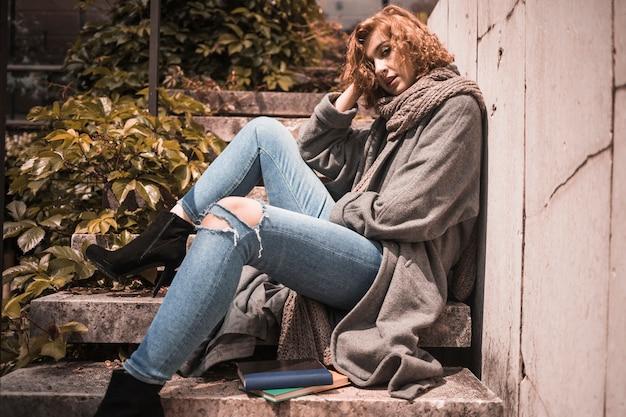 Mujer apoyada en la pared y durmiendo en pasos