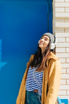 Mujer apoyada en la pared usando auriculares con los ojos cerrados