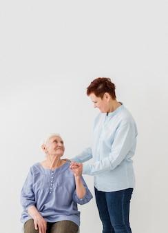 Mujer apoyando a una mujer mayor con espacio de copia
