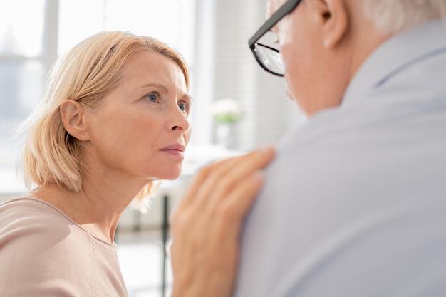 Mujer de apoyo rubia envejecida tocando el hombro de su paciente o compañero de grupo mientras escucha su historia