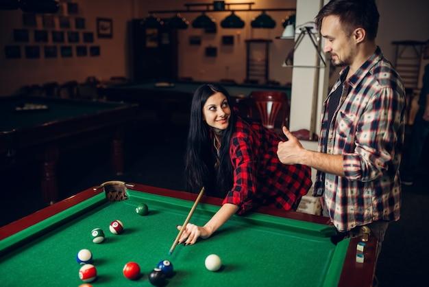 Mujer aprende a jugar al billar