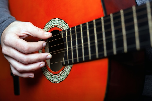 Una mujer aprende a tocar una guitarra acústica clásica de seis cuerdas. de cerca.