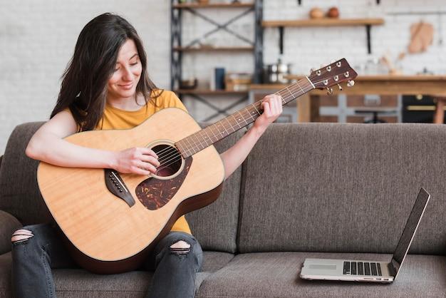Mujer aprendiendo en línea a tocar la guitarra