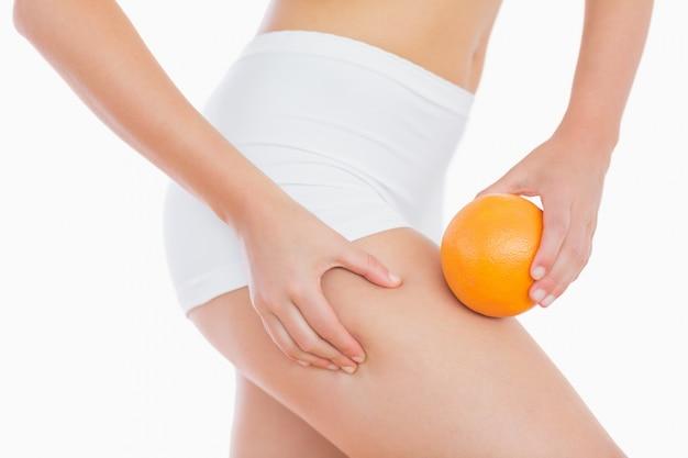 Mujer apretando grasa en el muslo mientras sostiene naranja