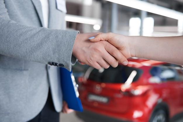 Mujer un apretón de manos con el vendedor en la sala de exposiciones