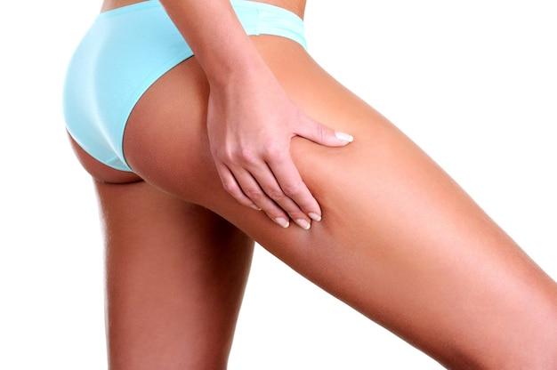 La mujer aprieta la piel de la cadera para controlar la celulitis - vista de perfil