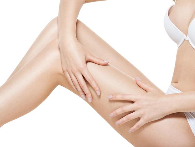 Mujer aprieta la piel de la celulitis en sus piernas en la pared blanca