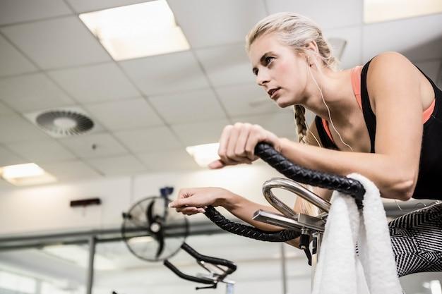 Mujer apta en bicicleta de ejercicio en el gimnasio