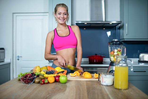 Mujer apta cortando frutas en la cocina