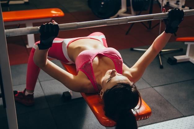 Mujer apta de los jóvenes que se resuelve con el barbell en banco en el gimnasio bar bench pres