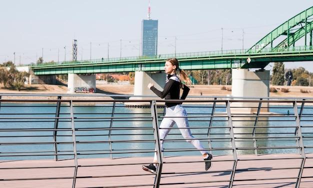 Mujer apta de los jóvenes en ropa deportiva que corre cerca del río idílico