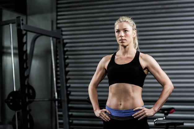 Mujer apta con las manos en las caderas en el gimnasio de crossfit