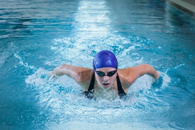 Mujer apta nadando en la piscina