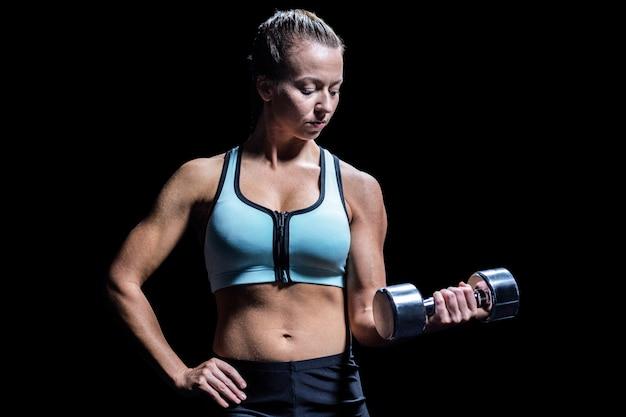Mujer apta que ejercita levantando pesa de gimnasia contra fondo negro