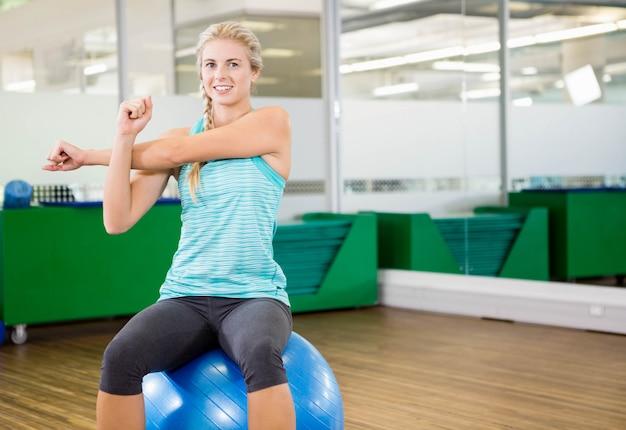 Mujer apta que estira y que se sienta en bola del ejercicio en estudio de la aptitud