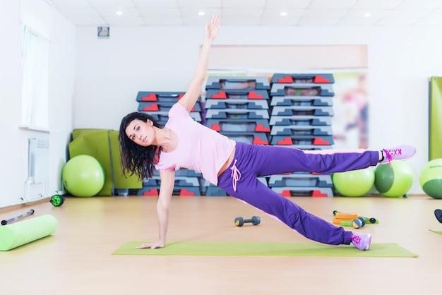 Mujer apta que hace ejercicio de la base del tablón que entrena detrás y presiona los músculos.