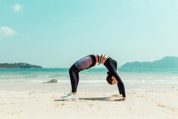 Mujer apta que hace estirar gimnástico en la playa. hermosa mujer haciendo yoga en el caluroso día de verano. phuket tailandia