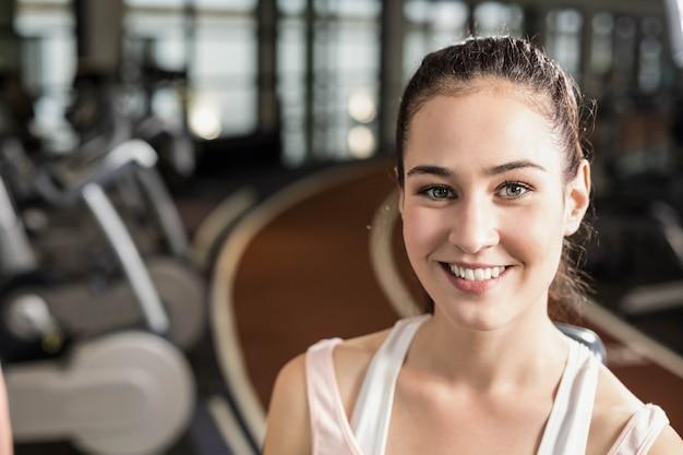Mujer apta que sonríe a la cámara en el gimnasio