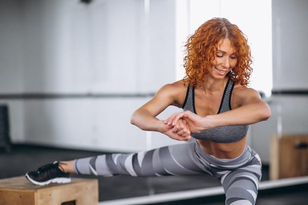 Mujer de la aptitud que estira en el gimnasio
