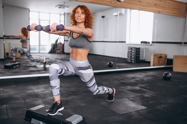 Mujer de la aptitud que hace estocadas con pesas de gimnasia en el gimnasio