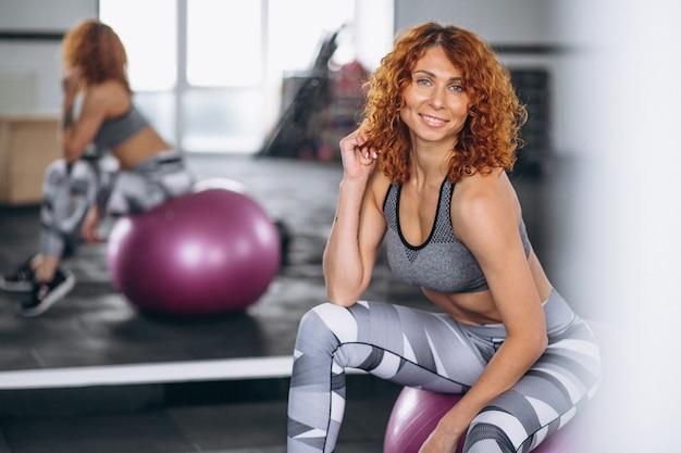 Mujer de la aptitud que se sienta en una bola de la aptitud en el gimnasio