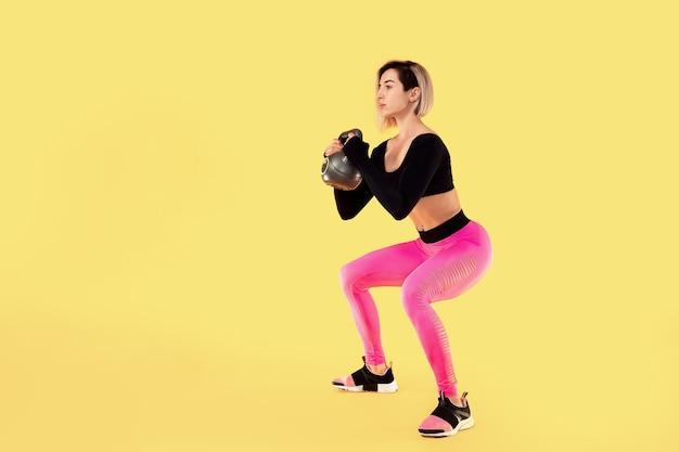 La mujer de la aptitud en ropa deportiva rosa y negra de moda trabaja con pesas rusas en la pared amarilla. fuerza y motivación.