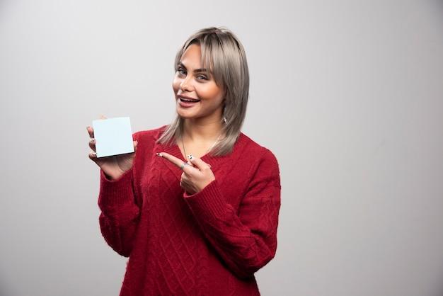 Mujer apuntando al bloc de notas sobre fondo gris.