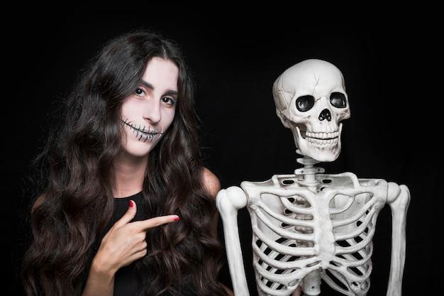 Mujer apuntando al esqueleto