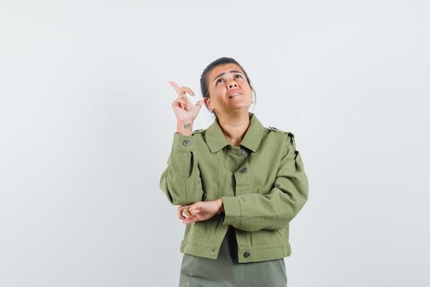 Mujer apuntando hacia arriba en chaqueta, camiseta y mirando enfocado