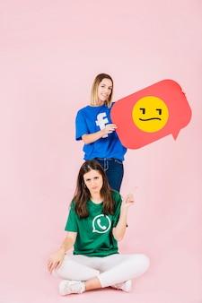 Mujer apuntando hacia arriba en frente de su amigo sosteniendo el bocadillo de diálogo emoji triste