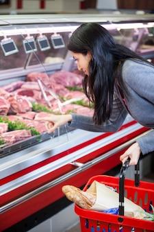 Mujer apuntando a la carne en la pantalla.