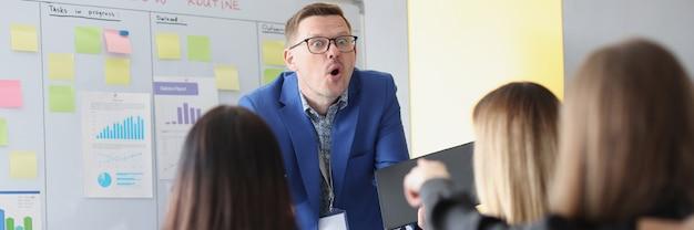 Mujer apuntando con el dedo al entrenador sorprendido en la formación empresarial