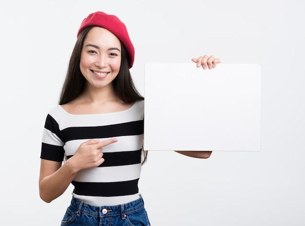 Mujer apuntando a la hoja de papel en blanco