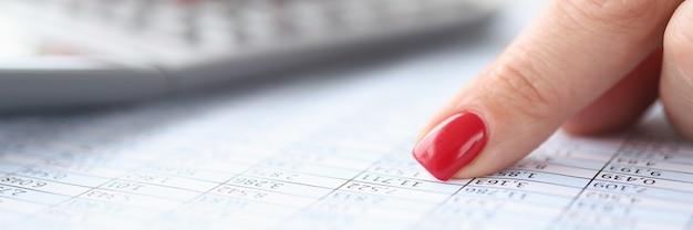 Mujer apuntando con su dedo índice a los números en la tabla y contando con calculadora de negocios de primer plano
