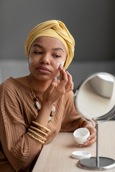 Mujer árabe aplicando crema en la cara. tratamiento de belleza