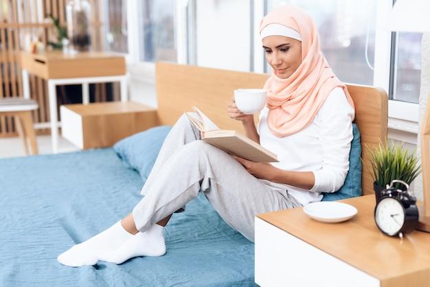 Mujer árabe está bebiendo té y leyendo un libro.