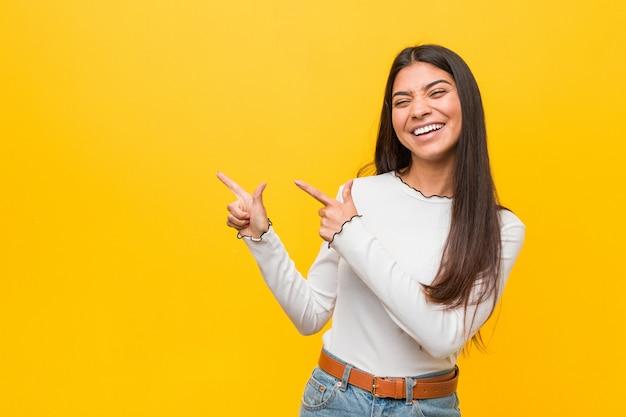 Mujer árabe bonita joven contra un fondo amarillo que señala con los índices a un espacio de la copia, expresando el entusiasmo y el deseo.
