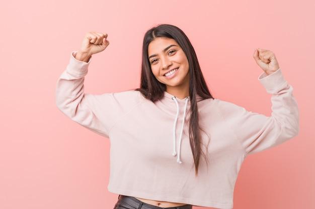 Mujer árabe bonita joven que lleva una mirada casual del deporte que muestra gesto de la fuerza con los brazos, símbolo del poder femenino