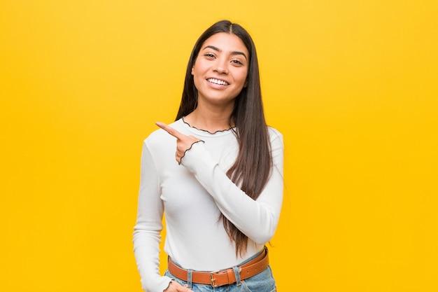 Mujer árabe bonita joven que sonríe y que señala a un lado, mostrando algo en el espacio en blanco.