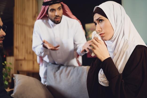 Mujer árabe con esposo en la recepción del psicólogo