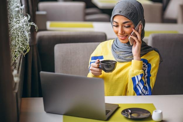 Mujer árabe en hijab dentro de un café trabajando en una computadora portátil