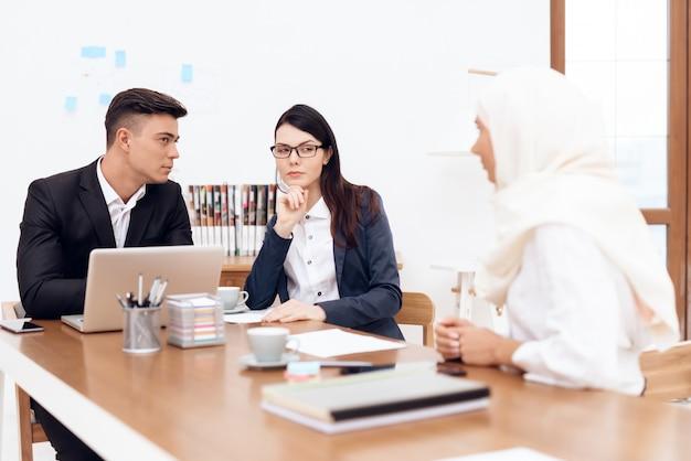 Mujer árabe en hijab trabaja con colegas en la oficina.