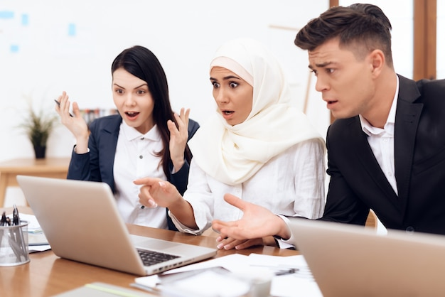 Una mujer árabe en hijab trabaja juntas en la oficina.