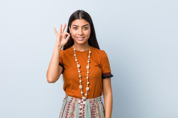 Mujer árabe joven alegre y confidente que muestra gesto aceptable.