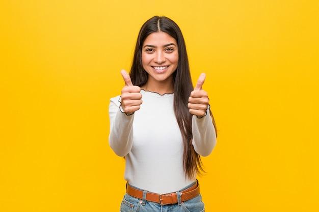La mujer árabe joven bonita contra un amarillo con los pulgares sube, anima sobre algo, apoya y respeta el concepto.